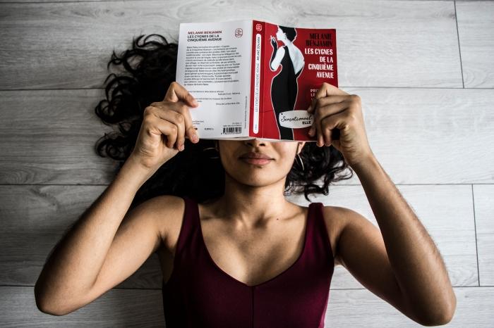 Chloé Andrianarisoa lisant Les cygnes de la cinquième avenue, allongée sur le sol © Chloé Andrianarisoa
